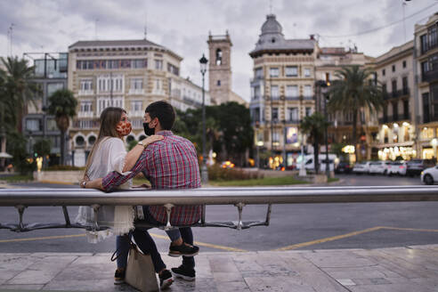 Couple sitting on bench in city - SASF00124