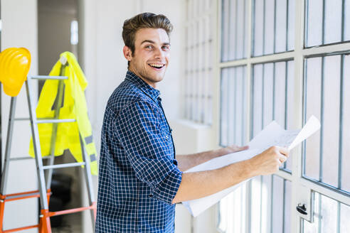 Smiling man holding blueprint while standing by window at construction site - GIOF08858