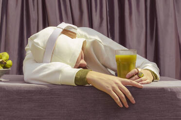 Woman with green juice listening music over headphones while lying on table at home - ERRF04447