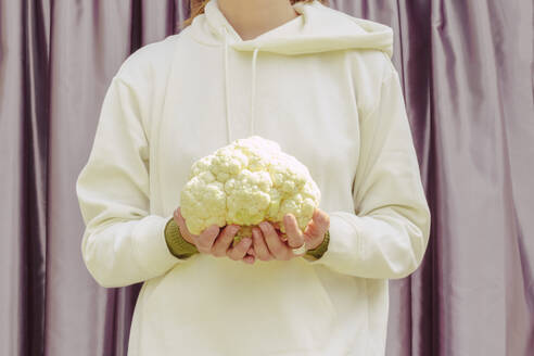 Close-up of mid adult woman holding cauliflower while standing against curtain at home - ERRF04450