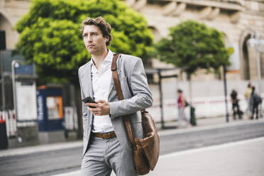 Man with bag using mobile phone while walking in city - UUF21566