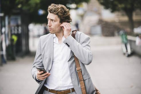 Man adjusting in-ear headphones while standing at sidewalk in city - UUF21569