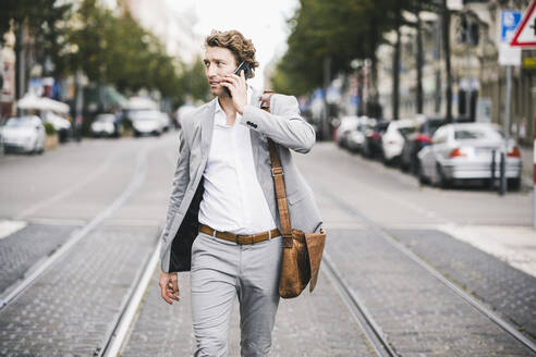 Man with bag talking on mobile phone while walking at tramway in city - UUF21572