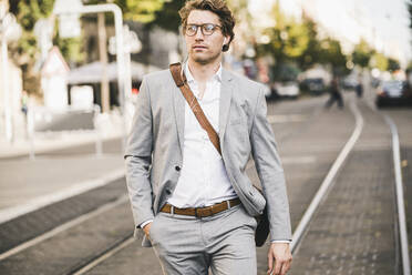 Handsome man with hands in pockets walking on tramway in city - UUF21578
