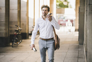 Smiling man talking on phone while walking at building in city - UUF21581