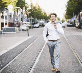 Businessman walking with hand in pocket and jacket over shoulder in city - UUF21587