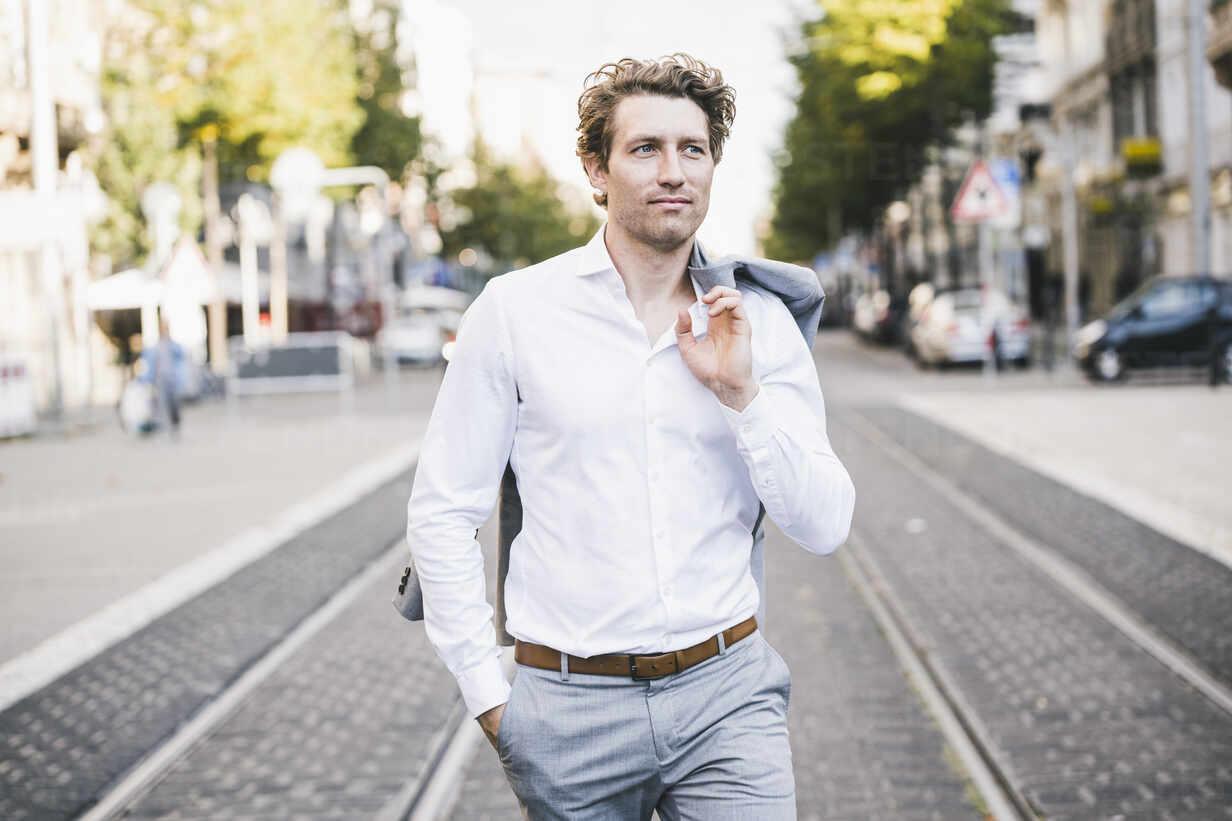 Smiling man walking with hand in pocket and jacket over shoulder in city - UUF21590 - Uwe Umstätter/Westend61