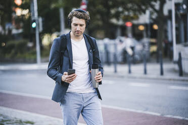 Man with headphone using mobile phone while walking on street in city - UUF21593