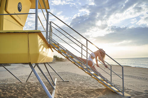 Woman exercising on staircase of lifeguard hut on beach - VEGF02915