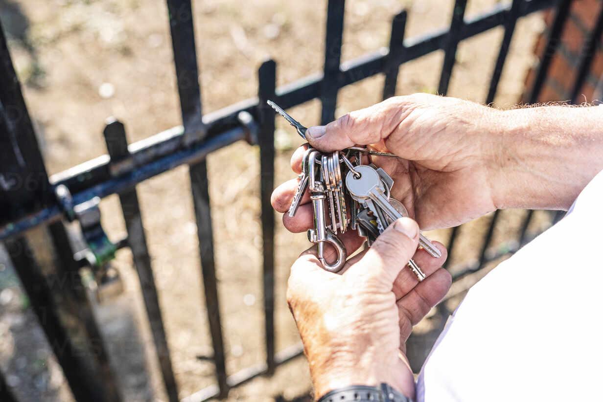 Hands of senior man holding keys at gate of vegetable garden - JCMF01491 - Jose Luis CARRASCOSA/Westend61