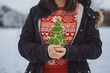 Close-up of young woman holding Christmas tree and lights while standing outdoors during winter - JSCF00158