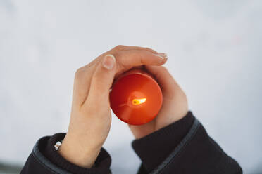 Close-up of young woman hands holding candle over snow covered land - JSCF00161