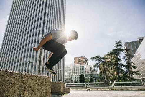 Young man performing parkour over retaining wall against Torre Picasso in city - ABZF03330