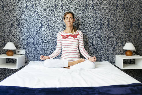 Mid adult woman meditating in lotus position on bed against patterned wall at home - JSMF01711