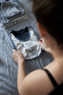 Pregnant woman folding baby clothes on bed at home - BZF00583