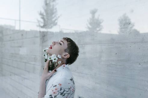 Gender fluid man standing behind glass while holding bouquet of daisies looking up against wall - TCEF01146