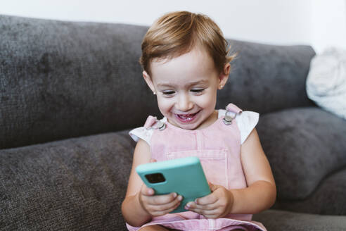 Smiling baby girl using mobile phone while sitting on sofa at home - EBBF00776