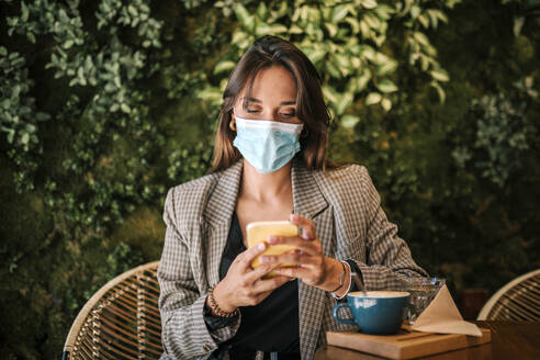 Woman text messaging on smart phone wearing protective face mask while sitting in cafe - GRCF00368