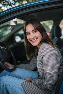 Smiling young woman looking out while sitting in car - GRCF00383