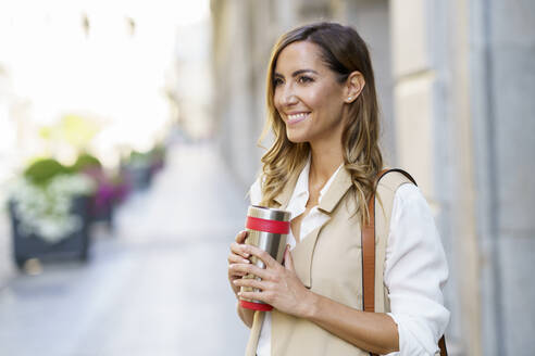 Smiling woman holding metal thermos while standing at sidewalk in city - JSMF01715
