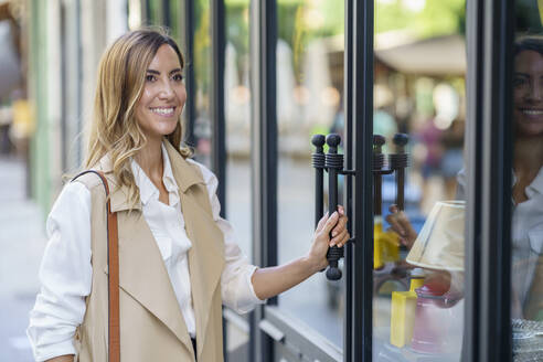 Smiling woman standing at store door in city - JSMF01724