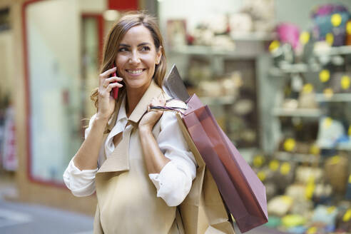 Smiling woman talking on phone while carrying shopping bag in city - JSMF01730