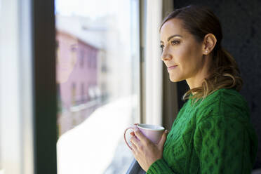 Woman holding coffee cup while standing by window at home - JSMF01748