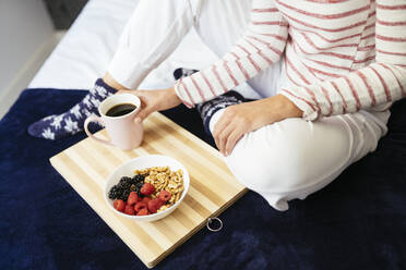Woman sitting with breakfast and coffee on bed at home - JSMF01751