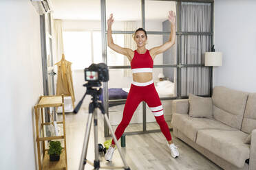 Woman looking at camera while exercising at home - JSMF01754
