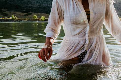 Woman walking through waist deep water with motion blue - CAVF89494