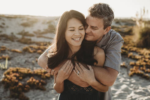 Loving husband with closed eyes embraces beautiful smiling wife - CAVF89563