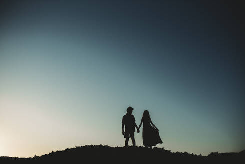 Silhouette of brother and sister standing on sand dune holding hands - CAVF89572
