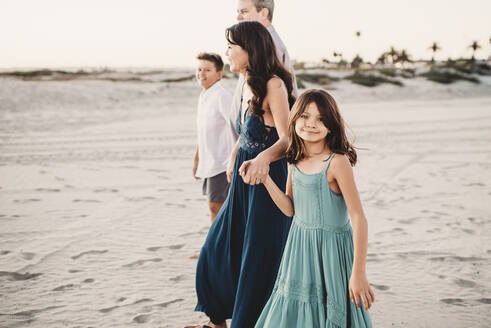 Happy family walking together on the beach holding hands - CAVF89584