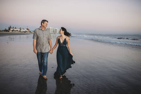Happy mid-40's couple gazing at each other while walking on the beach - CAVF89590