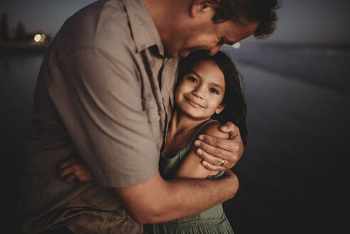 Loving father embracing beautiful 8 yr old daughter with dark eyes - CAVF89593