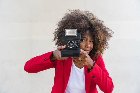 Woman taking picture from camera while standing against white wall - MGIF00974