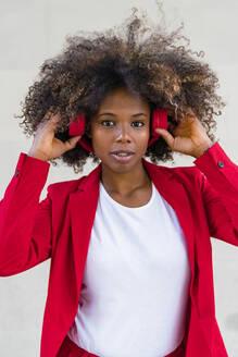 Woman listening to music through headphones - MGIF00977