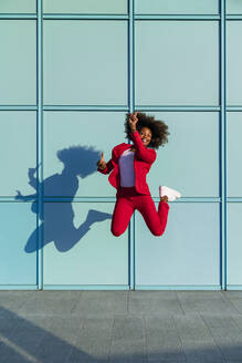 Woman enjoying while jumping against wall - MGIF01001