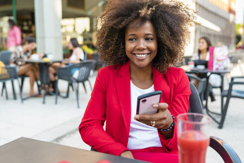 Smiling woman text messaging while sitting at sidewalk cafe - MGIF01013