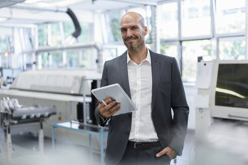 Smiling confident businessman holding digital tablet while standing with hand in pocket at bright factory - MOEF03293
