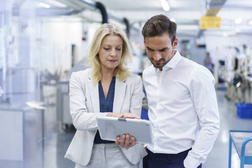 Confident blond businesswoman discussing over digital tablet with male colleague at factory - MOEF03296