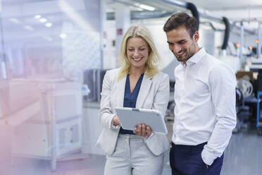 Smiling blond businesswoman discussing over digital tablet with young male colleague at factory - MOEF03299