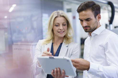 Blond businesswoman discussing over digital tablet with young male colleague at factory - MOEF03302