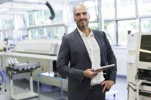 Confident businessman holding digital tablet while standing with hand on hip at illuminated factory - MOEF03320