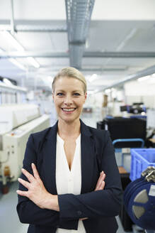 Smiling mature blond female professional standing with arms crossed at illuminated industry - MOEF03341