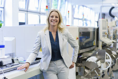 Smiling mature blond businesswoman standing by machinery at illuminated industry - MOEF03368