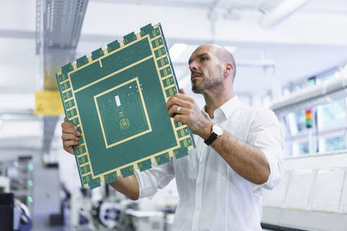Confident mature male technician looking at large circuit board while examining in illuminated factory - MOEF03377