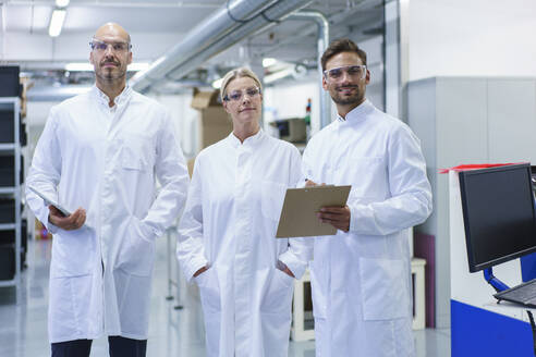 Confident male and female scientists standing in white lab coat at illuminated laboratory - MOEF03389