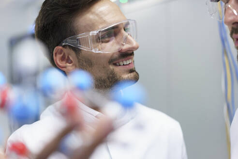 Smiling male scientist holding molecular structure while looking at colleague in illuminated laboratory - MOEF03395