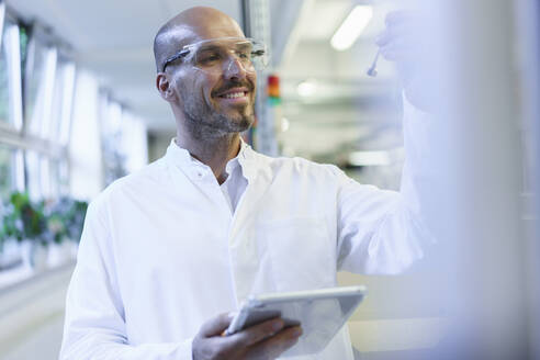 Smiling male scientist looking at sample while holding digital tablet in factory - MOEF03398